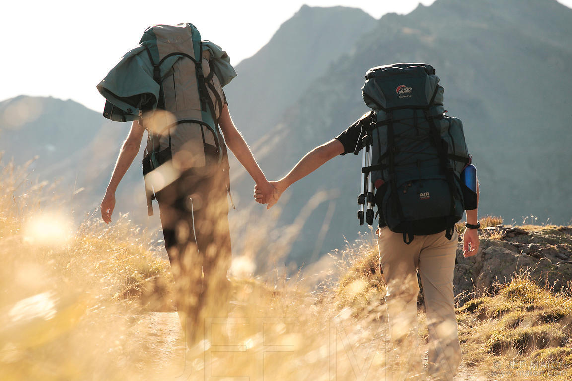 Backpackers couple walking hand in hand