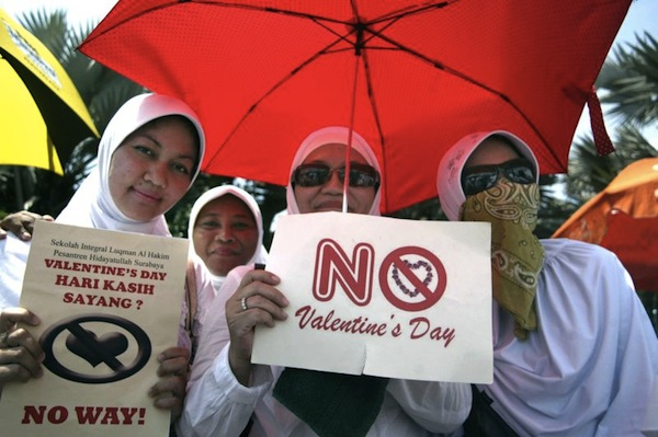 Indonesian female students from a local Islamic boarding school hold up anti-Valentine's Day placards during a protest in Surabaya, East Java province on February 13, 2012. Conservative Indonesian Islamic groups denounced Valentine's Day, saying it is un-Islamic, promoting promiscuity, casual sex and consumption of alcohol while other groups described the day as foreign cultural influence.    AFP PHOTO / JUNI KRISWANTO